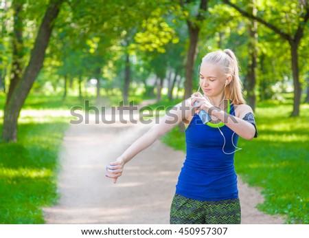Woman spraying insect repellents on skin before run