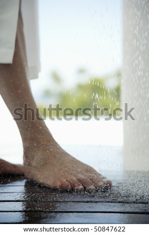 Woman standing under outdoor shower, low section