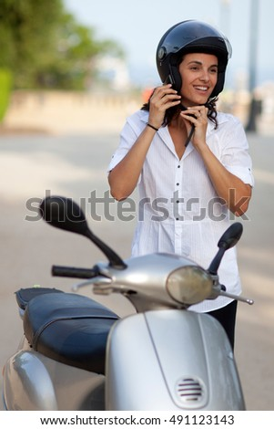 Woman takes off helmet on scooter