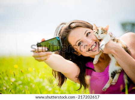 Woman taking photo with mobile phone camera of herself and her cat - outdoor in nature