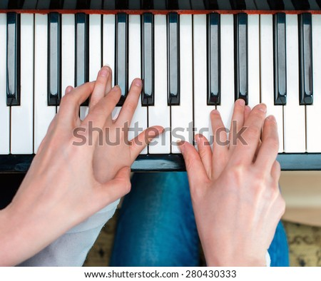 Woman teaching little girl to play the piano. Top view.