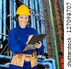 Woman technician with a clipboard in the refinery - stock photo