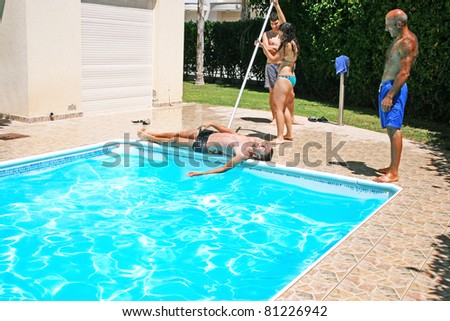 Woman  throwing  her friend to swimming pool.