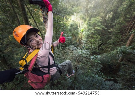 Woman Tourist Wearing Casual Clothing On Zip Line Or Canopy Experience In Laos Rainforest, Asia