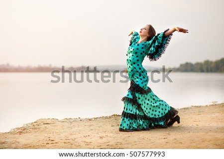 woman traditional dancer wearing green dress,dancing outside near the lake