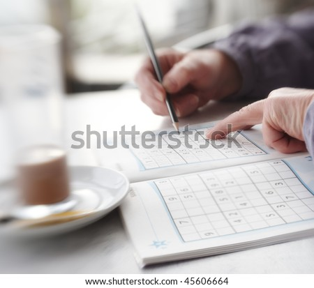 Woman trying to solve Sudoku Puzzle - window, sunlight, and coffee