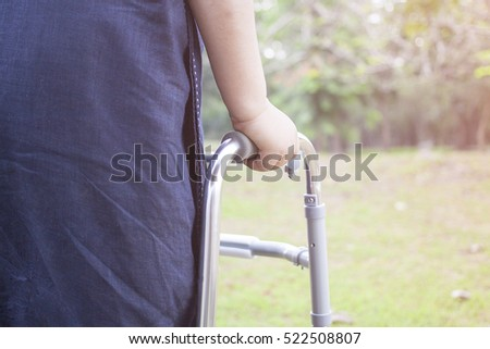 Woman using a walker with caregiver