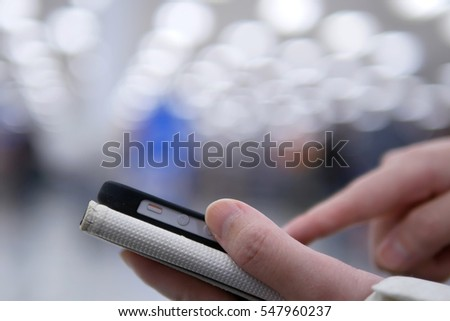 Woman using her mobile phone on beautiful blurred lighting background with bokeh shopping concept