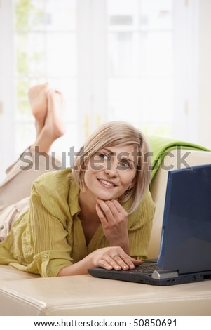 Woman using online chat on laptop computer from home.