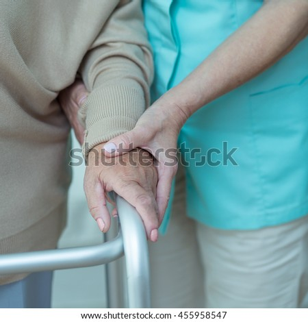 Woman using walking frame assisted by doctor