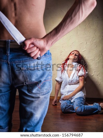 Woman victim of domestic violence and abuse. Husband holding a knife intimidates his wife