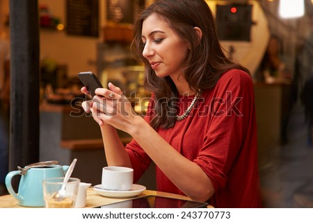 Woman Viewed Through Window Of Caf�¢?? Using Mobile Phone
