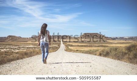 Woman walking on dirt road. Looking like a movie