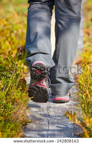 Woman walking on wooden path at swamp in Finland. Shoes close-up view.