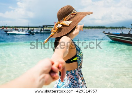Woman wanting her man to follow her in vacation or honeymoon to beach by the ocean
