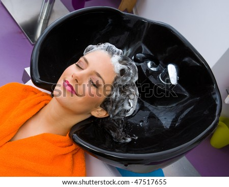woman washing hair in pool in hair salon