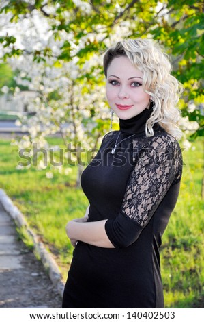 Woman wearing black dress over spring orchard