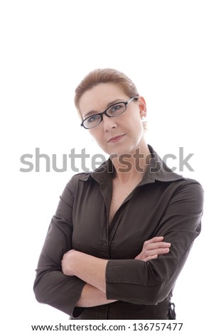 Woman wearing glasses standing with her arms folded looking at the viewer with an intent look, isolated on white