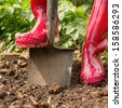 Woman wearing red rubber boots using shovel in her garden - stock photo