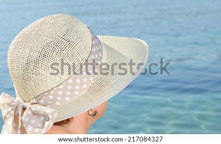 Woman with a hat facing the sea