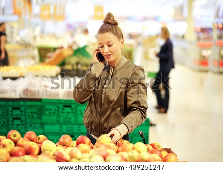 Woman with a smartphone  choosing vegetables at the market