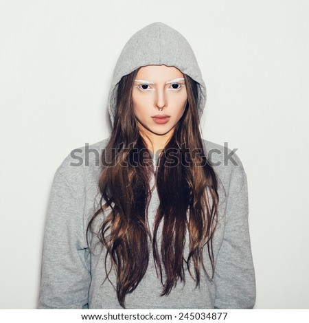 Woman with black eyes and white eyebrows. Hipster girl in grey hoodie, not isolated