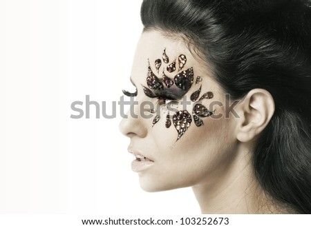 Woman with black hair and art make up on white background
