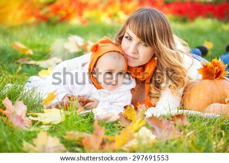 Woman with child in autumn park. Happy family. A young mother and her baby fall fun