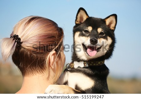 Woman with cute little Shiba Inu dog at riverside