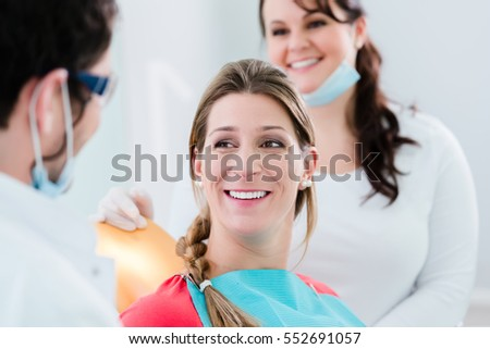 Woman with dentist and nurse smiling