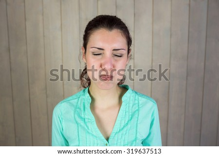 Woman with eyes closed while making face at home