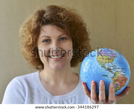 Woman with globe in hands thinking about a traveling
