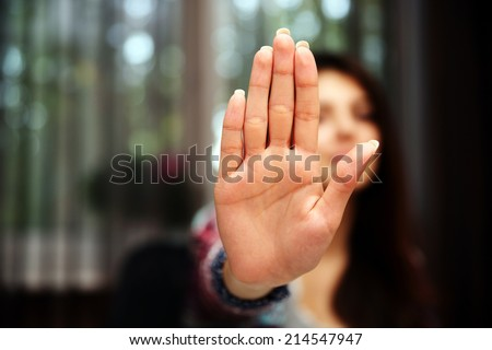 Woman with her hand extended signaling to stop (only her hand is in focus)