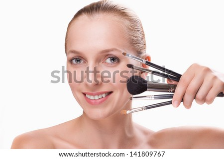 Woman with makeup brushes isolated