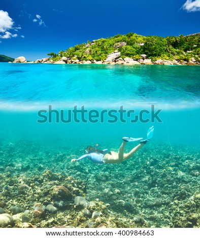 Woman with mask snorkeling in clear water at Seychelles