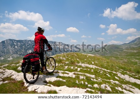 Woman with mountain bike on Alpine green valley