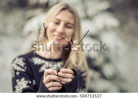 woman with sparkler at winter.