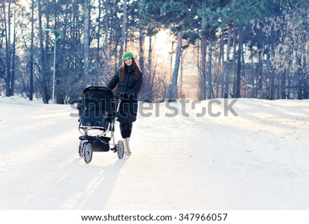 woman with stroller going for a walk in a park during lovely winter afternoon