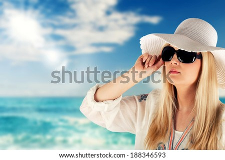 Woman With Sun hat and glasses At Beach