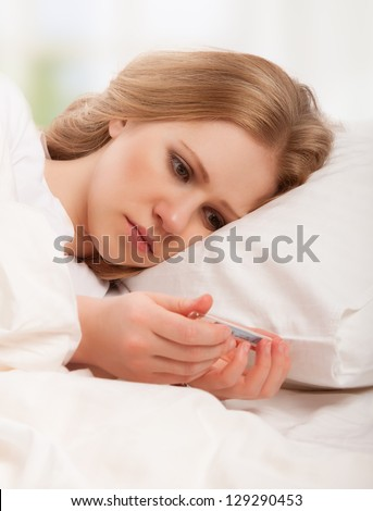 Woman with thermometer sick colds, flu, fever and migraine in bed