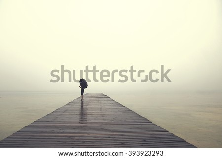 woman with umbrella contemplates peacefully in front of a lake