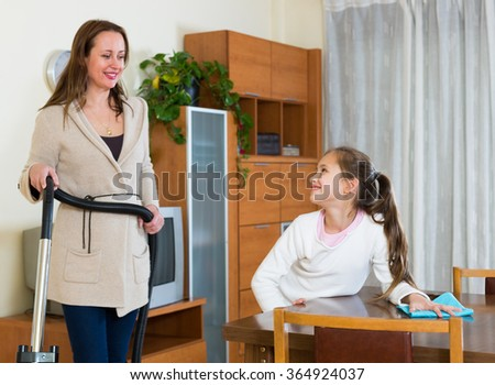 Woman with vacuum cleaner and smiling daughter with a rag at home