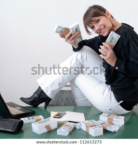 Woman with very excited look on her face holding money and sitting on desk at office. Packs of US dollars around her