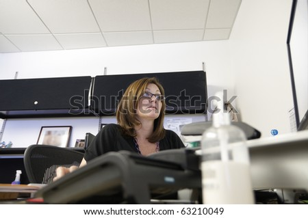 Woman working at her desk looking  little stressed