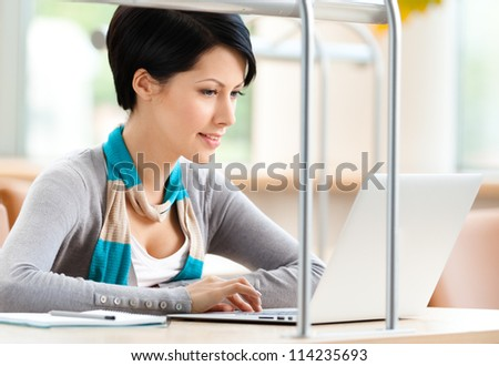 Woman working on the computer sitting at the desk at the reading hall