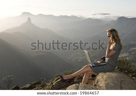 woman working with laptop in the forest and talking by phone