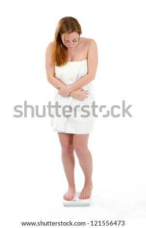Woman wrapped in a towel stands on a bathroom scale to check her weight.