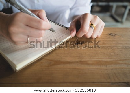 Woman writing in the notebook.