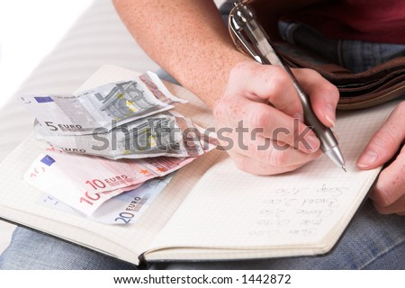 Womanhand writing down the expenses paid while some euro bills are lying on her household book