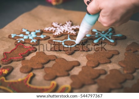 Womans hand decorating cookies with sugar. Making Gingerbread Cookies Series. - vintage effect